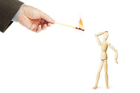 marioneta de madera: El hombre tiene miedo de fuego ardiente. Imagen abstracta con una marioneta de madera