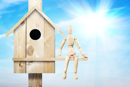 marioneta de madera: Man sitting next to wooden birdhouse. Abstract image with a wooden puppet Foto de archivo