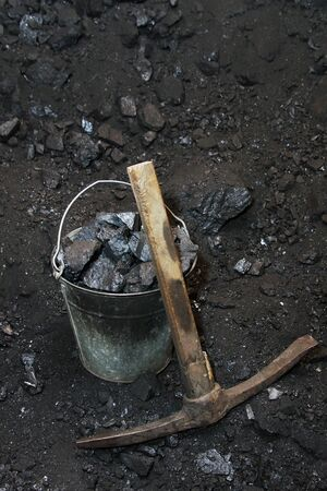 pickaxe: Retro coal mining. Pickaxe and the bucket full of lumps of coal in mine