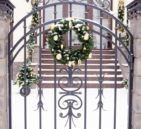 Traditional Christmas wreath with green fir tree twigs and golden New Year toys hangs on a gate outdoor Stock Photo