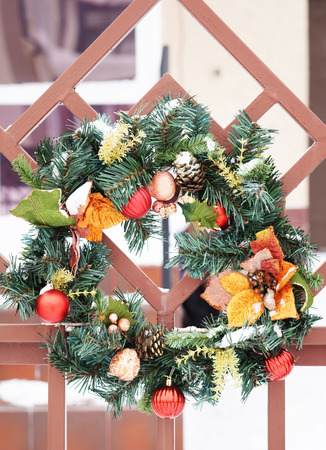 wicket: Traditional christmas wreath with green fir tree twigs and red balls hangs on a wicket outdoor Stock Photo