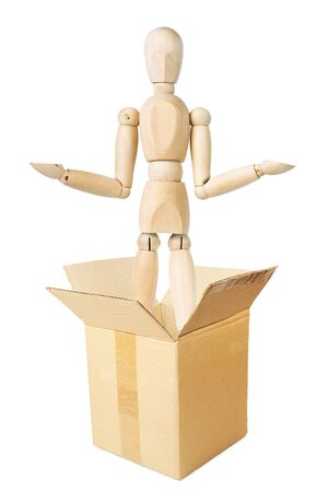 Man jumps out from the cardboard box. Abstract image with a wooden puppet