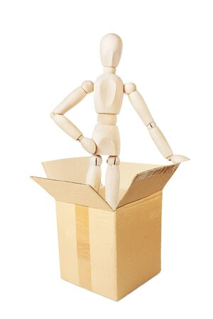 Man leaps out from the cardboard box. Abstract image with a wooden puppet