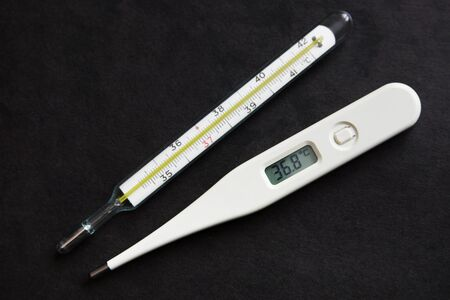 old mercury: Old mercury thermometer and new digital one on black background Stock Photo