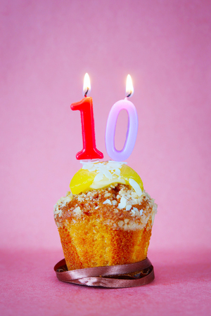 numero diez: Birthday cake with burning candle as number ten on pink background Foto de archivo