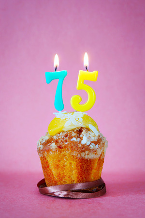 Muffin With Burning Birthday Candles As Number Seventy Five On Pink Background