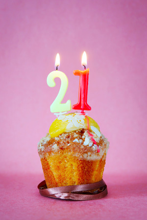 Muffin with burning birthday candles as number twenty one on pink background