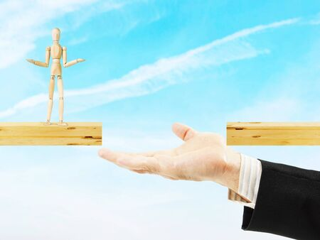 Man helps other to cross the chasm. Conceptual image with a wooden puppet