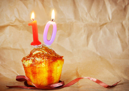 number ten: Birthday cake with burning candles as number ten on brown paper background