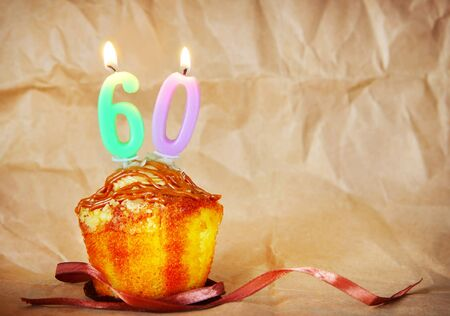 Birthday cake with burning candles as number sixty on brown paper background Stock Photo
