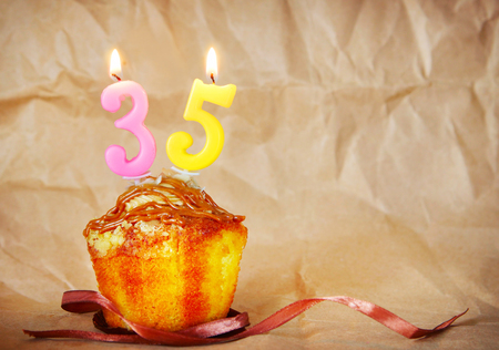 Birthday cake with burning candles as number thirty five on brown paper background