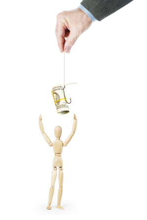 Man tempts another person with dollar banknotes on the fishing hook. Abstract conceptual image with a wooden puppet