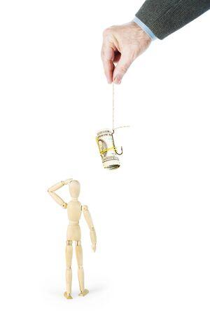 De man trekt een andere persoon met dollarbankbiljetten op de vishaak aan. Abstract conceptueel beeld met een houten pop Stockfoto