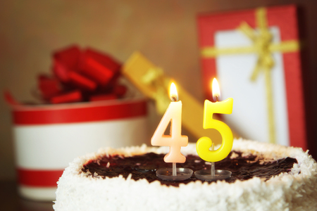 Fourty five years birthday. Cake with burning candles and gifts