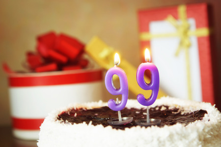 Ninety nine years birthday. Cake with burning candle and gifts Archivio Fotografico