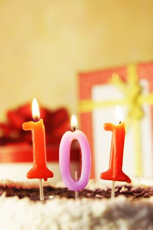 One hundred and one years. Birthday cake with burning candles and gifts