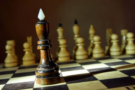 Black chess king in front of enemy team. Unequal fight. Concept with wooden chess pieces