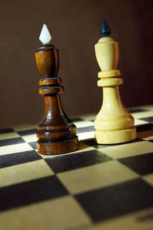 Two chess kings one in front of other. Fight of equal competitors. Concept with wooden chess pieces