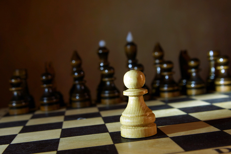 Lonely white chess pawn in front of enemy team. Boldness and courage. Concept with wooden chess pieces