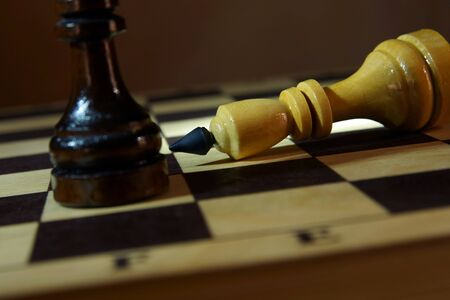 Chess king loses to adversary. Defeat and Victory. Concept with wooden chess pieces