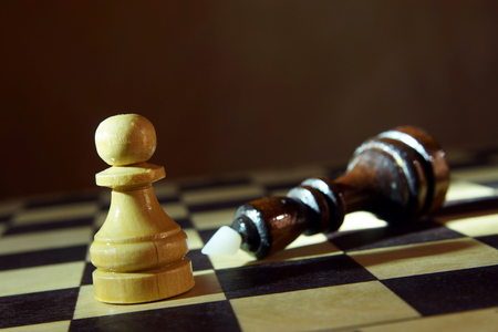 Chess king defeated by pawn. Victory in unequal fight. Concept with wooden chess pieces