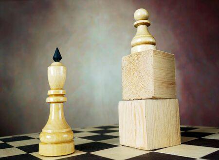 Superiority. Concept with chess pieces. Chess pawn has an advantage over chess king because he stands on a wooden stand