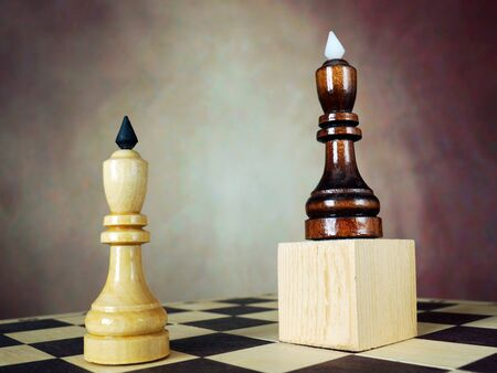 Superiority. Concept with chess pieces. One chess king has an advantage over another because he stands on a wooden stand Stock Photo