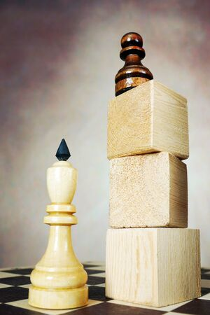 Supremacy. Concept with chess pieces. Chess pawn has an advantage over chess king because he stands on a high pedestal Stock Photo