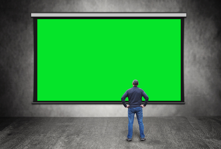 Man stands in front of big empty green screen Banque d'images