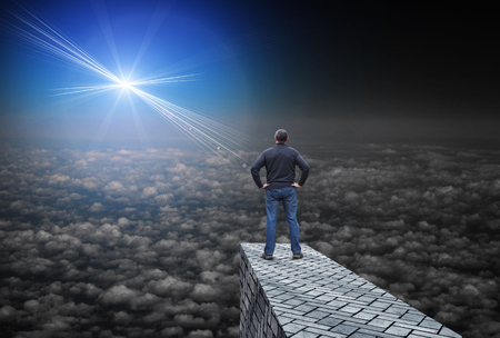 Far bright star illuminates the darkness, and the man standing above the clouds and looks at her