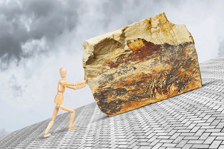 Man pushes the heavy and large stone upward along the slope with effort. Conceptual image with a wooden puppet Stock Photo - 102847206