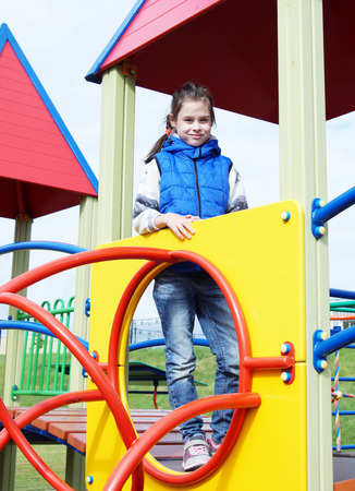 White little girl dressed in sleeveless jacket has fun at the playground outdoor in autumn