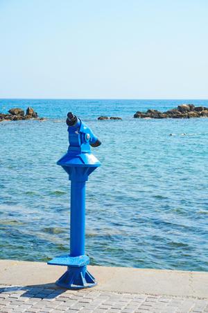 Blue tourist monocular for sightseeing on the seaside promenade
