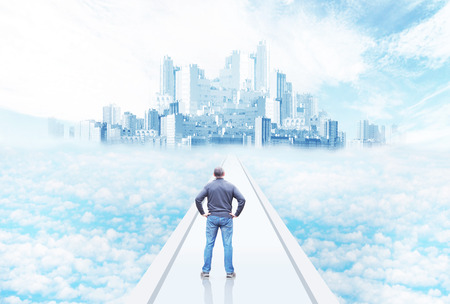 Man standing on the way to the city on the sky among clouds. Fantasy and dream Banco de Imagens