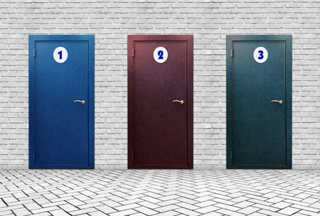 High brick wall in which three doors with different numbers Reklamní fotografie