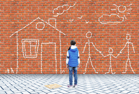 Little girl has drawn wit chalk on a brick wall picture with family and house 版權商用圖片