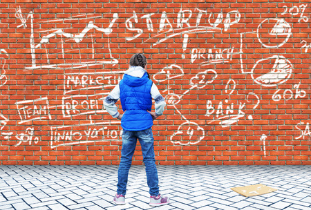 Little girl drew with chalk on a brick wall the drawing of a business startup with graphs and charts 写真素材