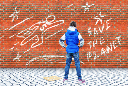 Little girl drew with chalk on a brick wall the drawing with a call Save the Planet 写真素材