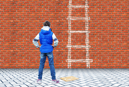 Little girl drew with chalk on a brick wall the ladder to overcome this wall as a obstacle