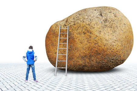 Little girl stands in front of a huge stone near which there is a ladder