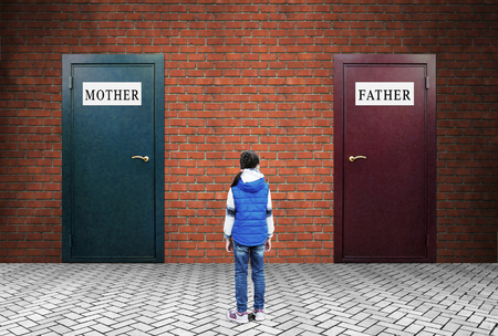 Family conflict. A little girl is standing in front of two closed doors with plates Mother and Father Stock Photo