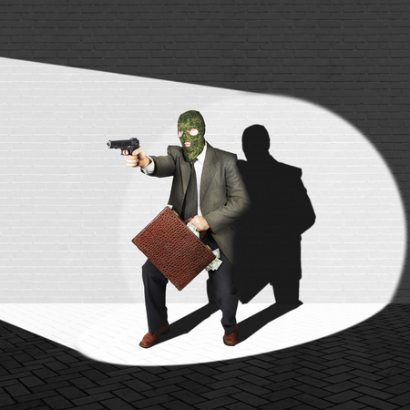 Disclosed thief with a pistol and a briefcase full of money in the spot of light