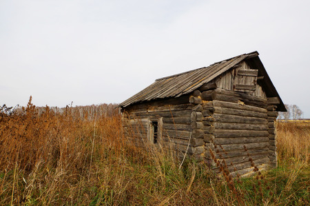 Autumn landscape with a lonely old dilapidated wooden house in the middle of the field Stock Photo