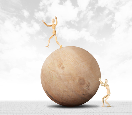 Man pushes a huge wooden ball and another tries not to fall from it. Abstract image with a wooden puppet Stock Photo