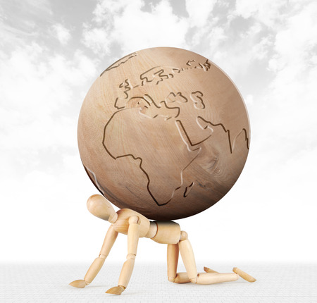 Man crawls on his knees with difficulty and on his back is a globe. Abstract image with a wooden puppet