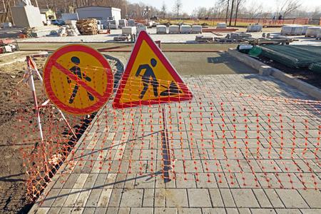 Reconstrucción de acera peatonal. Señales de advertencia sobre obras viales más adelante Foto de archivo