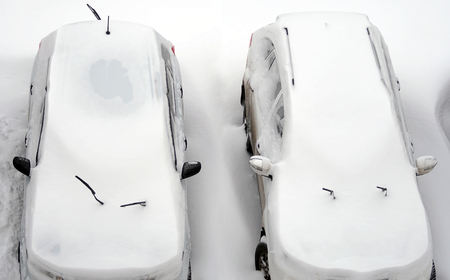 Top view on two snow covered cars after snowfall