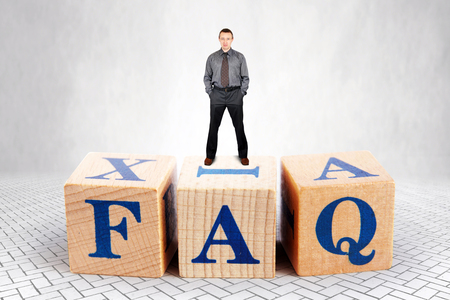 Self Confident adult Caucasian man stands on the top of heap of wooden blocks with letters FAQ