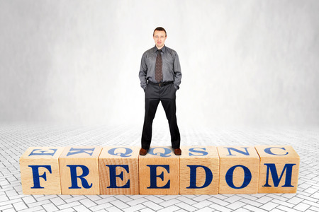 Self confident adult caucasian man stands on wooden blocks with a word Freedom