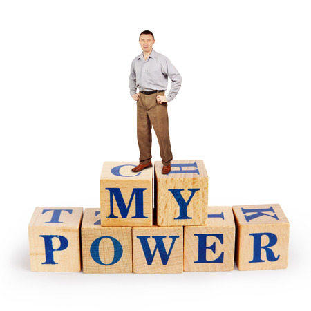 Adult caucasian man stands upon a heap of wooden blocks with words My Power Stock Photo